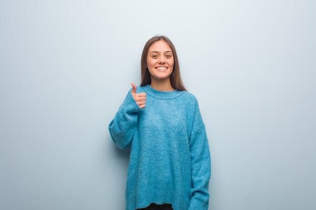 Молодая красивая женщина в синем свитере улыбается и поднимает палец вверх