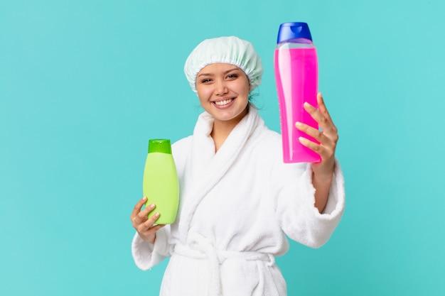 バスローブを着て、きれいな製品のボトルを保持している若いきれいな女性