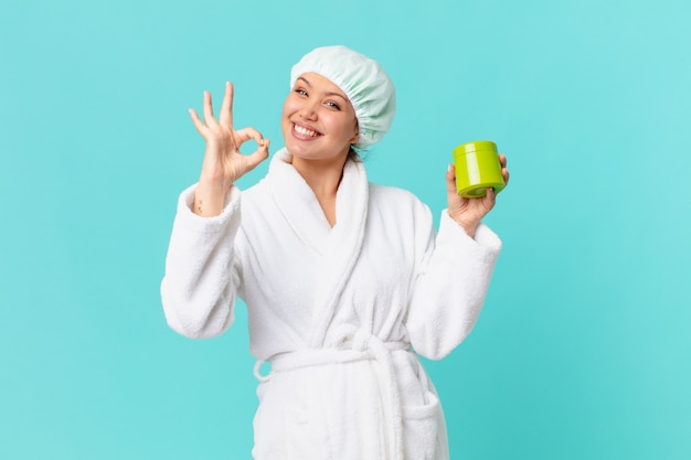 Young pretty woman wearing bathrobe and holding a clean product bottle