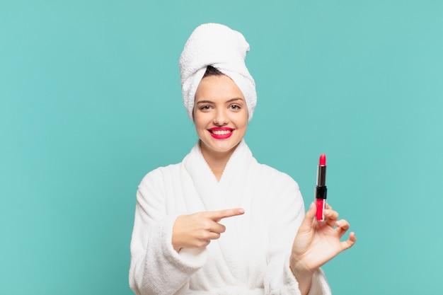 ポインティングまたはショーのバスローブと口紅を身に着けている若いきれいな女性