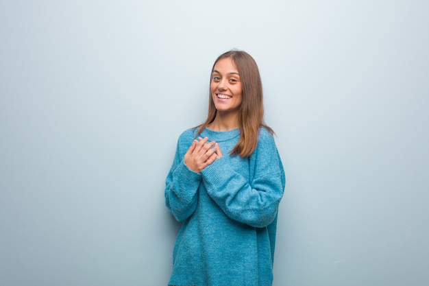 Young pretty woman wearing a blue sweater doing a romantic gesture