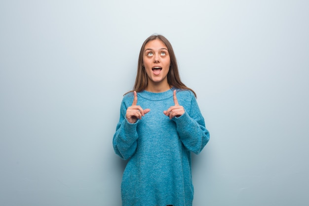 Young pretty woman wearing a blue sweater surprised pointing up to show something