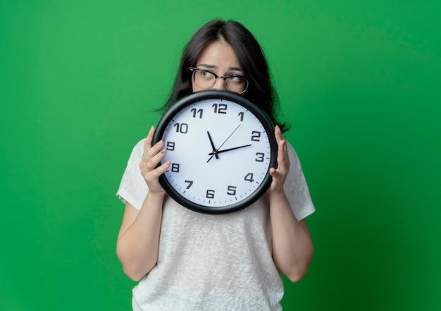 Giovane donna graziosa con gli occhiali tenendo l'orologio e guardando il lato da dietro l'orologio