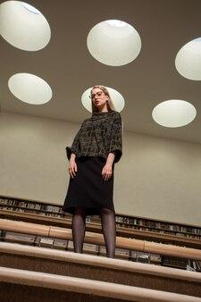 図書館の階段に立っている眼鏡をかけている若いきれいな女性。