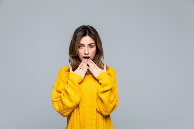 灰色の壁に分離された黄色のセーターを着ている若いきれいな女性