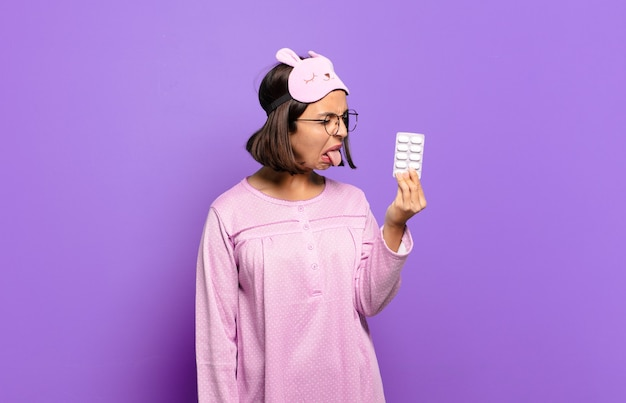 パジャマを着て薬を持っている若いきれいな女性