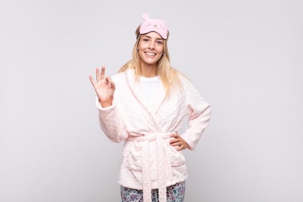 パジャマを着て、幸せ、リラックス、満足を感じ、大丈夫なジェスチャーで承認を示し、笑顔の若いきれいな女性