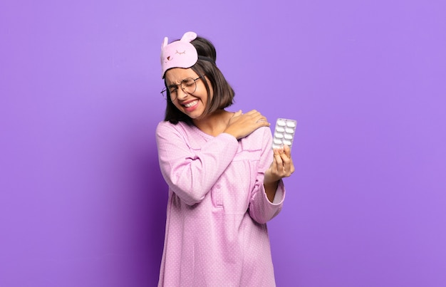 Young pretty woman wearing pajamas and holding pills