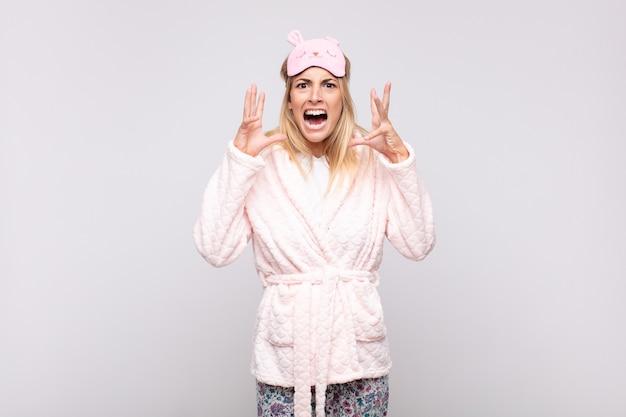Молодая красивая женщина в пижаме, кричащая с поднятыми руками, чувствуя ярость, разочарование, стресс и расстройство