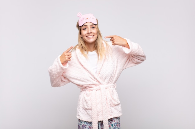 Young pretty woman wearing pajamas, smiling confidently pointing to own broad smile, positive, relaxed, satisfied attitude