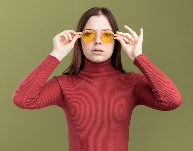Giovane bella donna che indossa occhiali da sole che guardano gli occhiali che afferrano davanti isolati sulla parete verde oliva