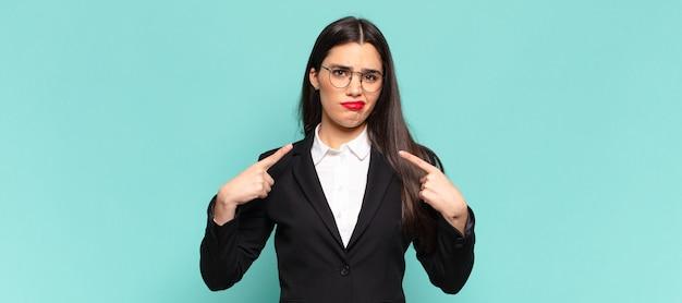자랑스럽고 공격적으로 보이는 나쁜 태도를 가진 젊은 예쁜 여성, 위쪽을 가리키거나 손으로 재미있는 표지판을 만들고 있습니다. 비즈니스 개념