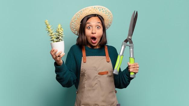 サボテンを持つ若いきれいな女性。農民の概念