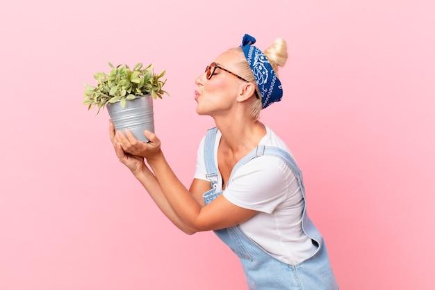 観葉植物を持つ若いきれいな女性