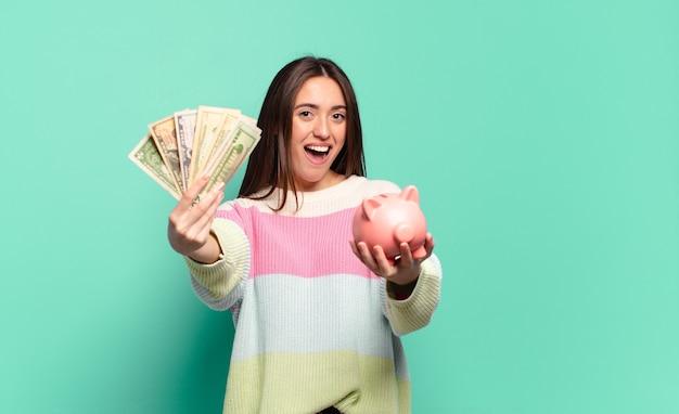 Молодая красивая женщина с копилкой и долларовыми банкнотами