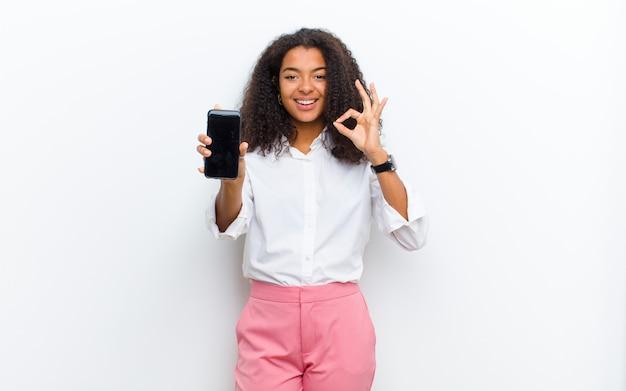 Молодая милая женщина с smartphone против белой стены