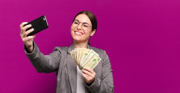Молодая красивая женщина с телефоном и долларовыми банкнотами. бизнес-концепция