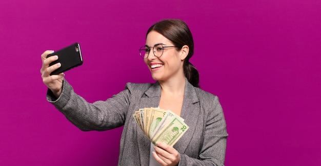 전화 및 달러 지폐와 영 예쁜 여자. 비즈니스 개념
