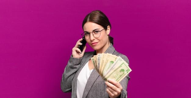 電話とドル紙幣を持つ若いきれいな女性。ビジネスコンセプト