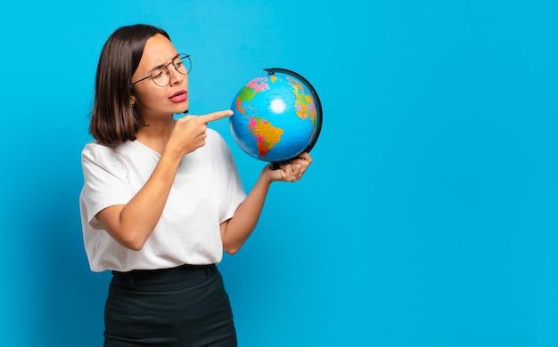 世界の地球地図を持つ若いきれいな女性