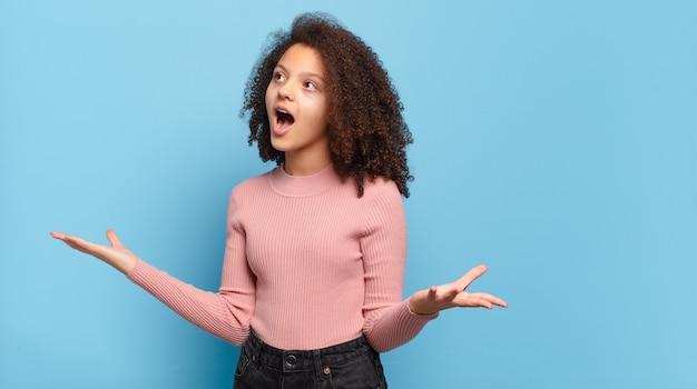 青い壁にポーズをとってアフロ髪とピンクのセーターを持つ若いきれいな女性