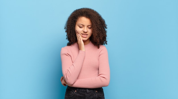 Молодая красивая женщина с афро-волосами и розовым свитером позирует на синей стене