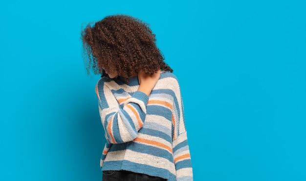 Молодая красивая женщина с афро-волосами и полосатым свитером позирует на синей стене