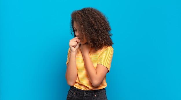 Молодая красивая женщина с афро-волосами и желтой рубашкой позирует на синей стене