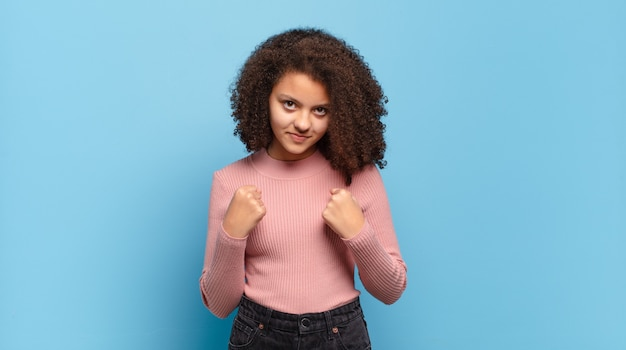 Young pretty woman with afro hair and pink sweater posing on blue wall