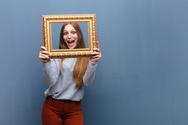 Young pretty woman with a baroque frame against blue wall with a copy space