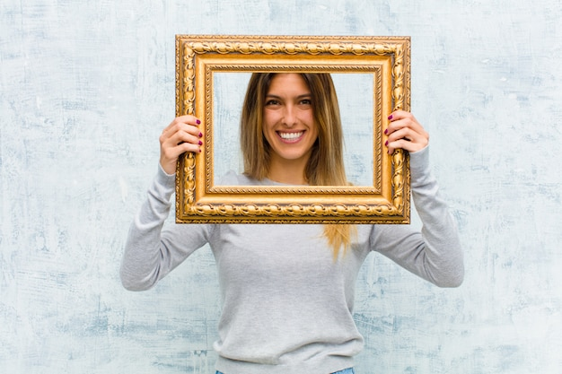 Young pretty woman with a baroque frame against grunge wall