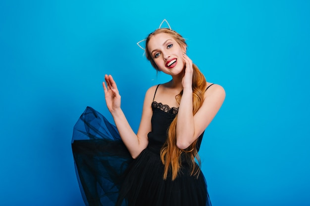 Young pretty woman with beautiful smile, fluttering black dress, posing. she has long hair, wearing headband with cat ears, nice make up with red lipstick.