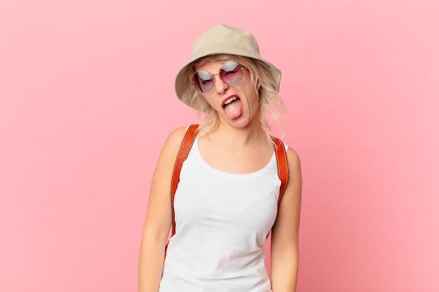 陽気で反抗的な態度、冗談を言ったり、舌を突き出したりする若いきれいな女性。夏の観光コンセプト