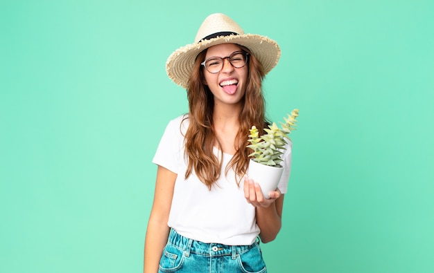 Молодая красивая женщина с веселым и бунтарским настроем, шутит и высунула язык в соломенной шляпе и держит кактус