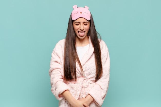 Молодая красивая женщина с веселым, беззаботным, бунтарским отношением, шутит и высунул язык, весело. концепция пробуждения в пижаме
