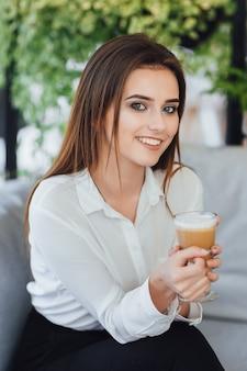 彼女の手にコーヒーを持ってオフィスに座っている白いシャツを着た若いきれいな女性。背景がぼやけています。