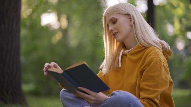 곱슬머리를 한 젊고 예쁜 여자는 자연에 관심을 가지고 모험 소설을 읽습니다. 여자는 푸른 잔디에 대한 책을 통해 leafs. 도시 밖의 여가. 따뜻한 여름날. 휴가. 클로즈업, 4k uhd.