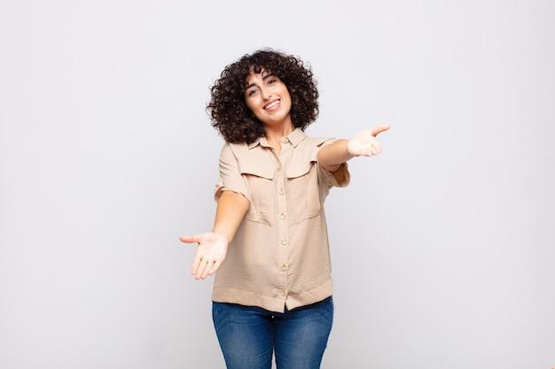 巻き毛とベージュのシャツを持つ若いきれいな女性