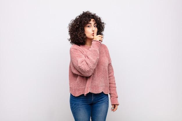 곱슬 머리와 분홍색 스웨터와 젊은 예쁜 여자