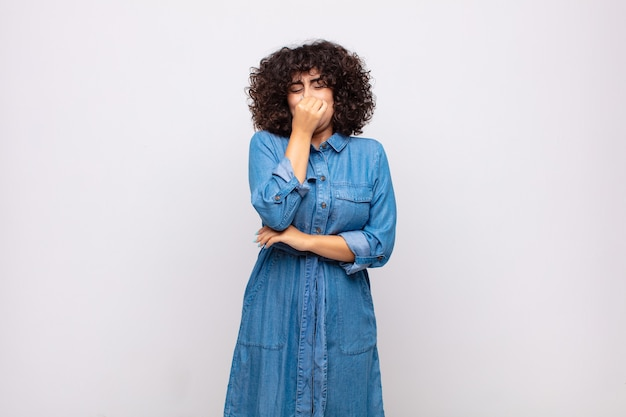 Young pretty woman with curly hair and jeans dress