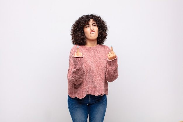 Young pretty woman with curly hair and offensive gesture