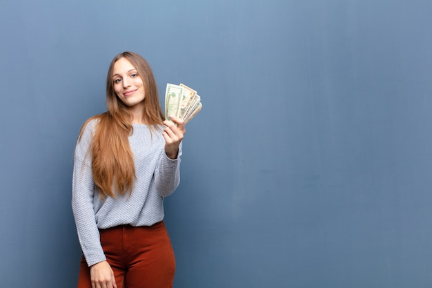 Young pretty woman with dollar banknotes against blue wall with a copy space