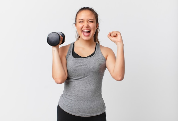 Young pretty woman with dumbbell