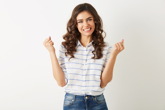 Young pretty woman with emotional face expression, holding hands up, success, winner, casual style, isolated, happy, positive mood, sincere smile, long curly hair, white teeth, strong, independed