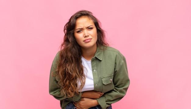 Молодая красивая женщина с зеленой джинсовой открытой рубашкой позирует на розовой стене