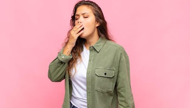 ピンクの壁にポーズをとって緑のデニムのオープンシャツと若いきれいな女性