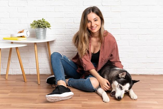 Молодая красивая женщина с ее хаски, сидя на полу в помещении