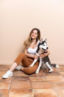室内の床に座っている彼女のハスキー犬を持つ若いきれいな女性