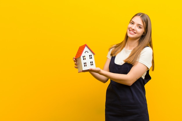 Young pretty woman with a house model against orange
