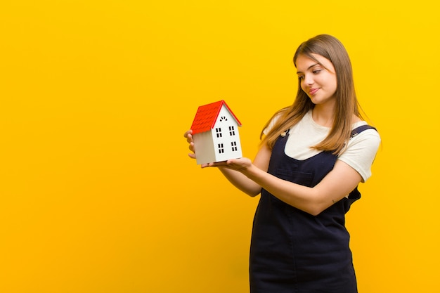 Young pretty woman with a house model  orange